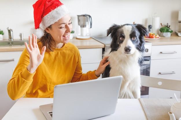 Hund und frau tragen die weihnachtsmütze, die handvideoanruffamilie durch webcam winkt