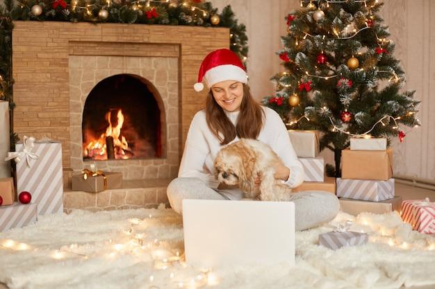 Hund und frau tragen roten hut, der videoanruf mit jemandem hat. mädchen mit laptop, das virtuellen versammlungschat an feiertagen sitzt, die auf wohnzimmer zu hause sitzen frohes weihnachten und neujahr.