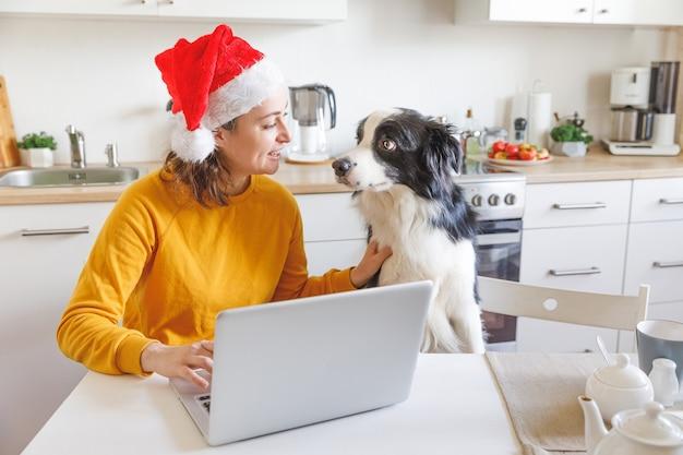 Hund und frau tragen weihnachtsmütze mit videoanruf familie durch webcam