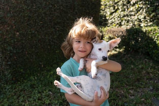 Hund und kind. welpe mit kind. glücklicher junge, der mit hund umarmt und spielt. anpassung für kinder.