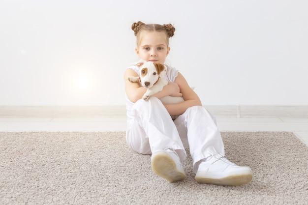 Hunde, haustiere und tierkonzept - kleines kindermädchen, das mit welpen jack russell terrier sitzt