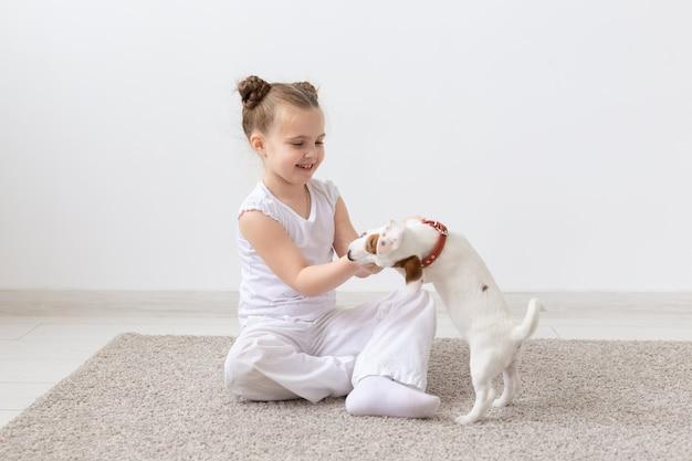 Hunde-, kinder- und haustierkonzept - kleines kindermädchen, das auf dem boden mit niedlichem welpen sitzt