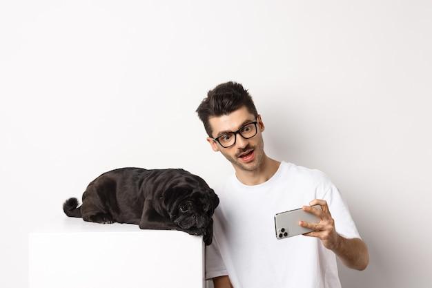 Hundebesitzer, der selfie mit niedlichem mops nimmt, fotos auf handy, weiß machend.