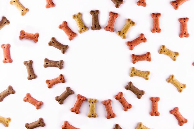 Hundefutter muster mit trockenen snacks in form von knochen gemacht. worthund in den hölzernen fliesen. lustige flache lagebeschaffenheit.