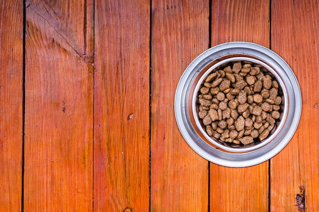 Hundenahrungsmittelschüssel auf hölzernem hintergrund mit kopienraum
