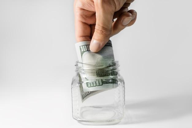 Hundert-dollar-schein in einem sparschwein. die person nimmt die letzte banknote