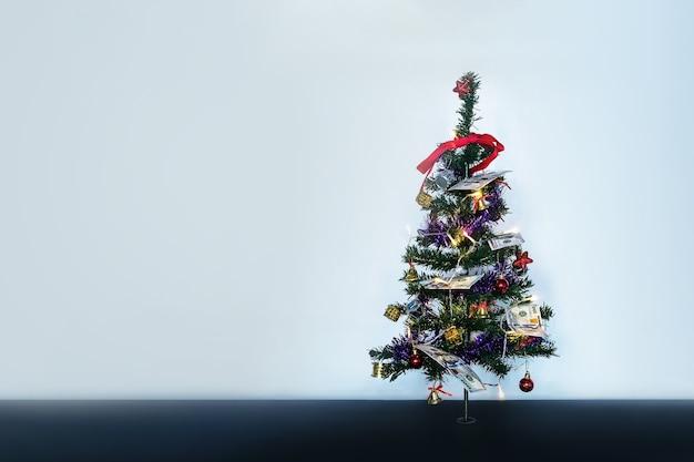 Hundert-dollar-scheine. geld am weihnachtsbaum. kleiner verzierter weihnachtsbaum auf blauem hintergrund. platz für textdesign kopieren