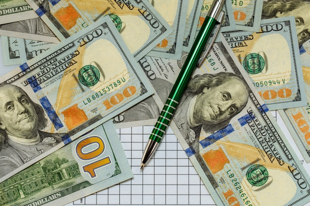 Hundert-dollar-scheine liegen mit grünem stift verstreut auf dem tisch.