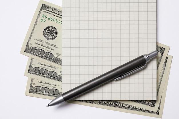 Hundert dollarnoten, quadratisches notizbuch, stift. geschäftskonzept mit kopierraum. auf weißem hintergrund isoliert.