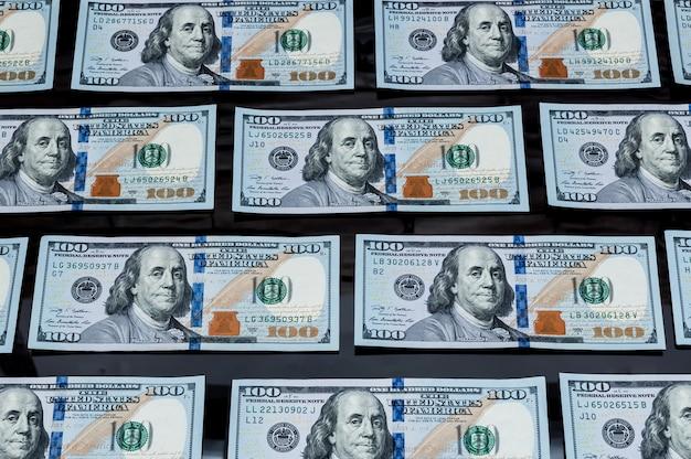 Hundert dollarscheine in folge auf einem schwarzen hintergrund ausgebreitet. von oben betrachten.