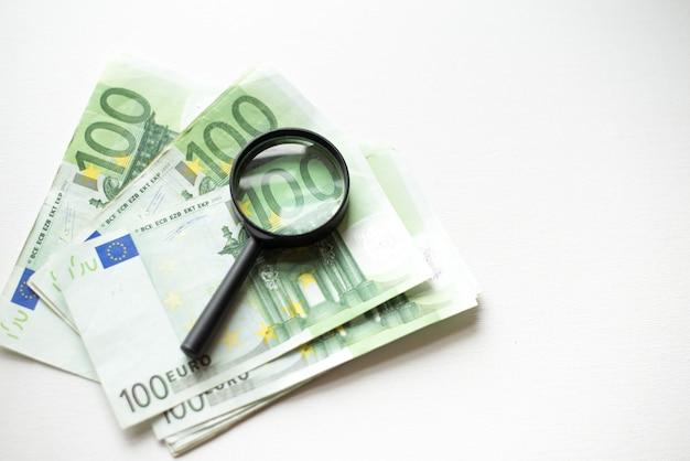 Hundert eurobanknote unter der lupe lokalisiert auf weißem hintergrund