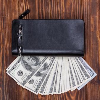 Hundert us-dollar-banknoten in schwarzer lederbrieftasche auf holzhintergrund