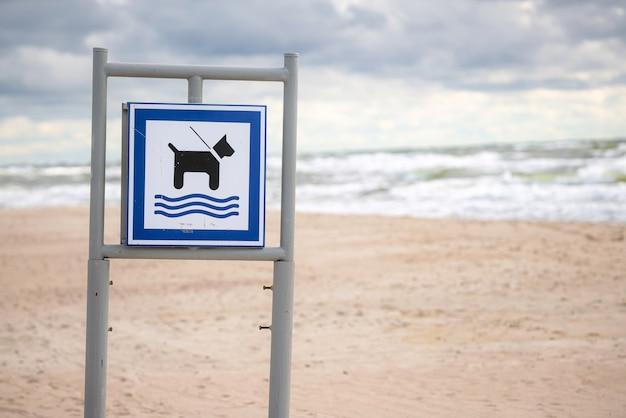 Hundestrandschild mit sand und wellen im rücken.