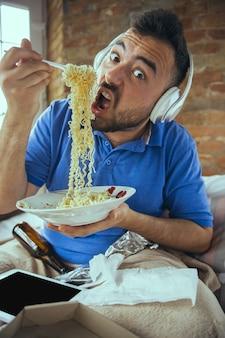 Hungrig essen instant-nudeln. fauler mann, der in seinem bett lebt, umgeben von unordnung. sie müssen nicht ausgehen, um glücklich zu sein. die verwendung von gadgets, das ansehen von filmen und serien sieht emotional aus. tablet mit exemplar für anzeige.