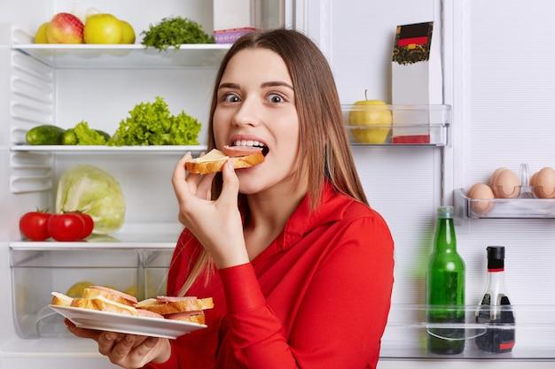 Hungrige entzückende frau isst köstliche sandwiches mit käse und wurst, steht in der nähe des geöffneten kühlschranks voller produkte. schöne frau hat hunger nach der arbeit. menschen und esskonzept
