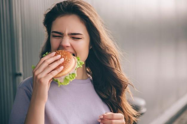 Hungrige frau beißt stück burger
