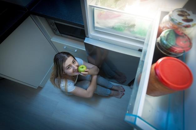 Hungrige frau, die spät in der nacht apfel auf dem küchenboden isst