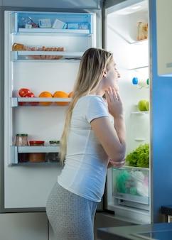 Hungrige frau, die spät in der nacht in den offenen kühlschrank schaut