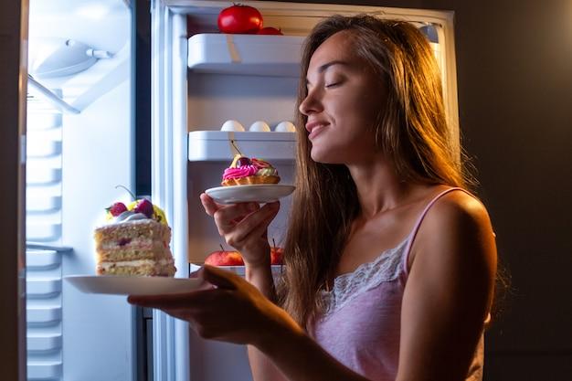 Hungrige frau im pyjama isst mehlprodukte in der nacht nahe kühlschrank. stoppen sie die diät und nehmen sie aufgrund von kohlenhydraten und ungesunder ernährung zusätzliche pfunde zu