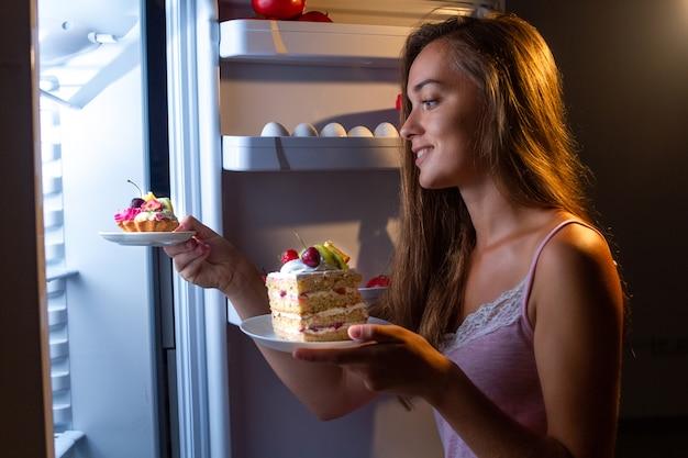 Hungrige frau im pyjama isst und genießt kuchen in der nacht in der nähe von kühlschrank. stoppen sie die diät und nehmen sie aufgrund von kohlenhydraten und ungesundem nachtessen zusätzliche pfunde zu