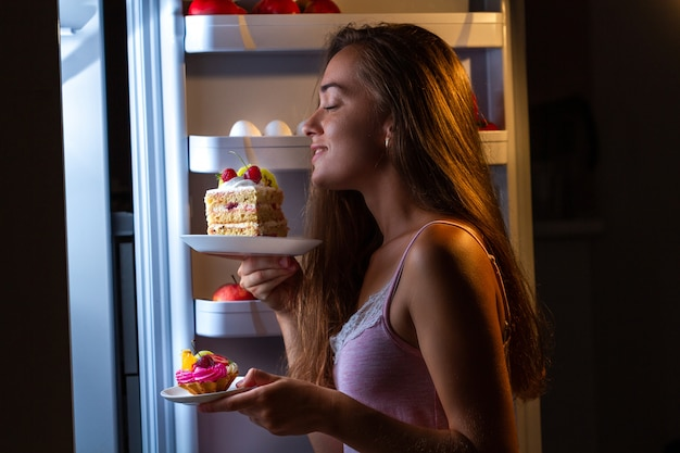 Hungrige frau im pyjama isst und genießt mehlprodukte nachts in der nähe des kühlschranks. stoppen sie die diät und nehmen sie aufgrund von kohlenhydraten und ungesunder ernährung zusätzliche pfunde zu