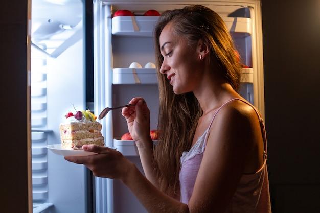 Hungrige frau im schlafanzug, die süßen kuchen nachts nahe kühlschrank isst. stoppen sie die diät und gewinnen sie zusätzliche pfunde aufgrund von junk food mit hohem kohlenhydratgehalt und ungesundem nachtessen
