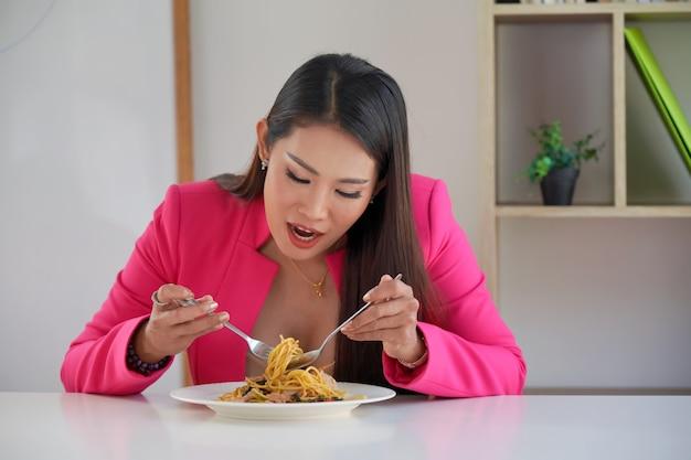 Hungrige geschäftsfrau, die spaghetti isst. ein teller mit nudeln und eine gabel isst wild nudeln. geschäftsleute oder büroangestellte mit italienischem essen in der mittagspause.