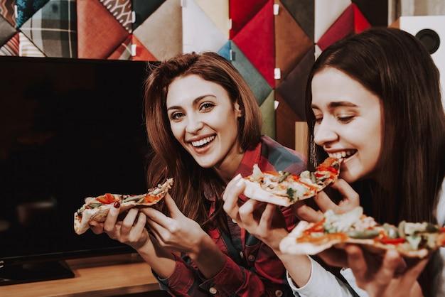 Hungrige junge firma, die pizza auf einer party isst.