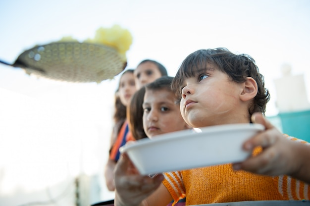 Hungrige kinder werden von wohltätigkeitsorganisationen ernährt