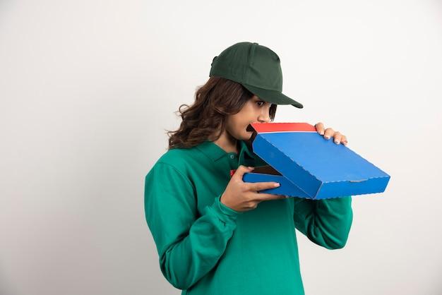 Hungrige lieferfrau, die pizzakasten auf weiß öffnet.