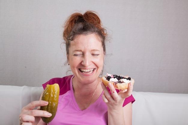 Hungrige lustige schwangere frau, die viele verschiedene lebensmittel isst