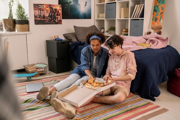 Hungrige teenager sitzen auf dem boden neben dem bett und essen pizza