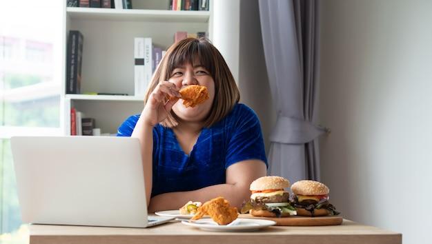 Hungrige übergewichtige frau, die gebratenes huhn hält, nachdem liefermann lebensmittel zu hause liefert