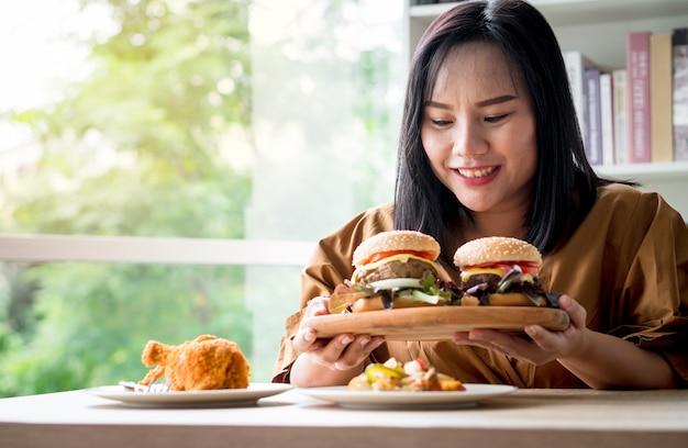 Hungrige übergewichtige frau, die hamburger auf holzteller hält, nachdem liefermann lebensmittel zu hause liefert.