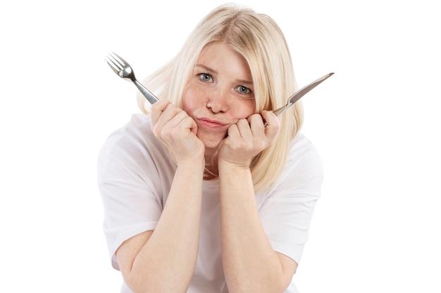 Hungrige umgekippte junge frau mit einer gabel und einem messer in ihren händen, die an einem leeren tisch sitzen. isoliert auf weißem hintergrund