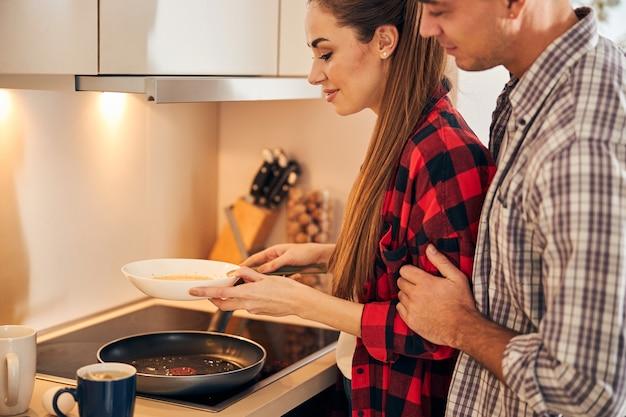 Hungriger ehemann sieht ihrer frau beim omelett zu