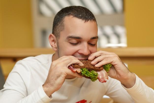 Hungriger junger mann im restaurant essen sandwich