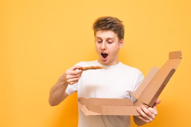 Hungriger kerl mit pizza in seinen händen ist auf einem gelben isoliert