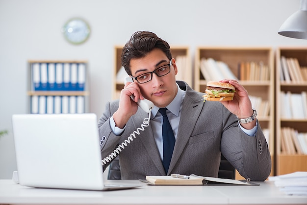 Hungriger lustiger geschäftsmann, der sandwich der ungesunden fertigkost isst