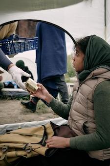 Hungriger mädchenflüchtling, der konserven aus der behandschuhten hand eines freiwilligen nimmt