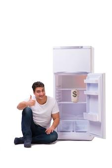 Hungriger mann, der nach geld sucht, um den kühlschrank zu füllen