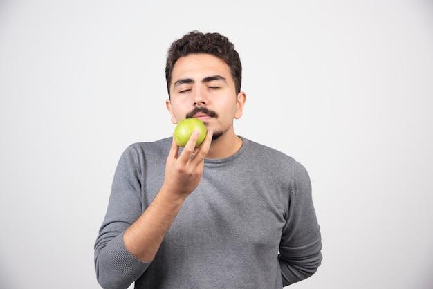Hungriger mann riecht grünen apfel auf grau.