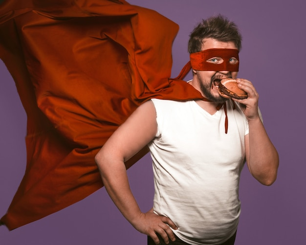 Hungriger superheld mann isst großen hamburger mit fleisch. mann im roten fliegenden umhang isst, der kamera auf traubenpurpurhintergrund betrachtet. fast-food-snack-konzept