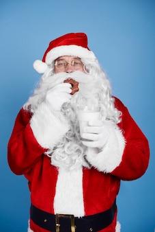Hungriger weihnachtsmann, der keks am studioschuss isst