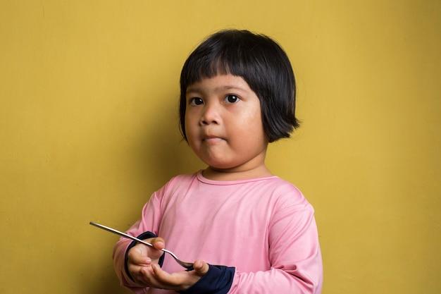 Hungriges asiatisches mädchen, das einen löffel auf gelber wand hält