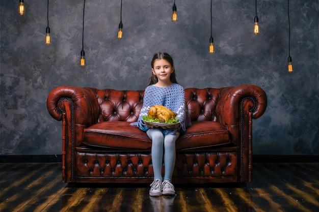 Hungriges kind mit leckerem gebratenem huhn in der hand
