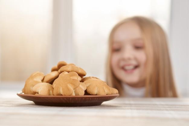 Hungriges mädchen mit dem blonden geraden haar und den großen braunen augen schaut auf köstlichen blumen-förmigen plätzchen auf weißer tabelle.