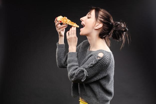 Hungriges mädchen mit geöffnetem mund pizza essend