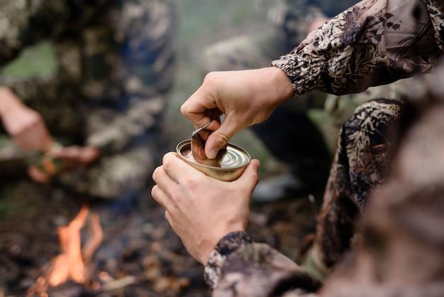 Hunter opening tin in der nähe von bonfire rest nach der jagd.