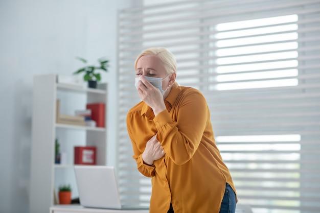 Husten, infektion. unglückliche frau in einer schutzmaske, die hustet und ihre augen mit ihrer hand auf ihrer brust bedeckt, die in der arztpraxis steht